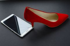 Red shoes and broken phone on grey background.  stock photo