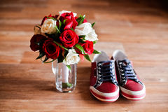 Red shoes on a brown floor with  bouquet of roses Royalty Free Stock Photo