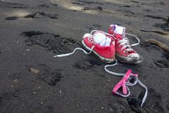 Red shoes and girls sunglasses on Waipio Valley black sand beach, Hawaii. Sandy red shoes and girls sunglasses on Waipio Valley black sand beach, Hawaii big Royalty Free Stock Photos