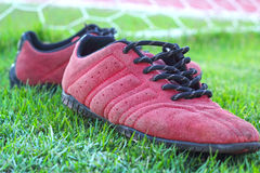 Red shoes on green grass with goal football.  Royalty Free Stock Photo
