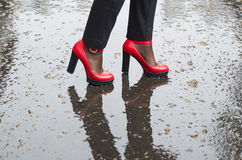 Red shoes high-heeled on wet asphalt. stock photo