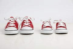 Red Shoes isolated on white. Two pairs of red canvas shoes isolated on white. One big and one small. Big brother concept Royalty Free Stock Photography