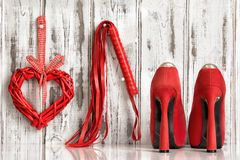 Red shoes lash heart handcuffs on a wooden background royalty free stock images