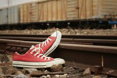 Red shoes leaning on the train tracks. Stock Photos
