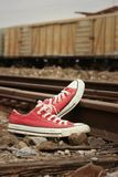 Red shoes leaning on the train tracks. Stock Photography