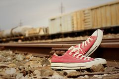 Red shoes leaning on the train tracks. Stock Image