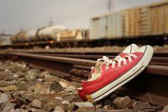 Red shoes leaning on the train tracks. Royalty Free Stock Image