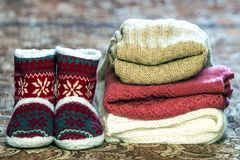 Red shoes with new year pattern and a pile of knitted sweaters royalty free stock photography