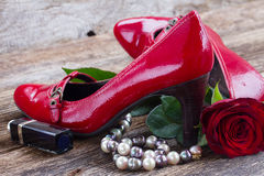 Red shoes with rose flower. Pair of red shoes with rose  and pearl jewellery on wood Stock Photos