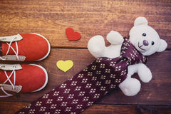 Red shoes son with white teddy bear and necktie. On rustic wooden background, father`s day concept royalty free stock photography