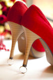 Red shoes with stiletto heels on silver wedding rings. Red or crimson fabric shoes with stiletto heels or high heels on silver wedding rings Royalty Free Stock Photography