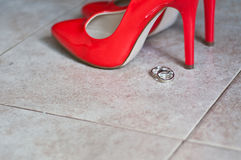 Red shoes and wedding rings Royalty Free Stock Images