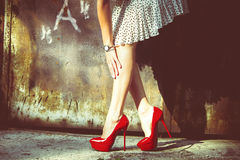Red shoes. Woman legs in red high heel shoes and short skirt outdoor shot against old metal door Stock Images