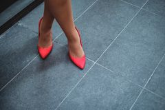 Red shoes on a woman`s legs. Standing on tiling Stock Photography