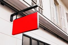 Red shop logo sign on the wall. Outside Stock Images