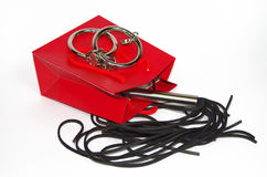 Red shopping bag with flogging whip and handcuff Royalty Free Stock Photography