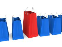 Red shopping bag in a row of blue bags Stock Photo