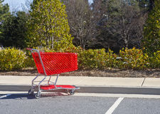 Red Shopping Cart in Parking Lot Stock Photo