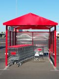Red shopping trolley shelter. In a contrast of blue sky and shiny metal royalty free stock images