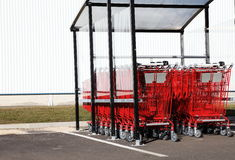 Red Shopping Trolleys. Outdoors under a glass enclosure with a white building facade behind  for copy space Royalty Free Stock Photo