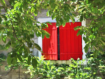 Red shutters. Half closed on a house facade sunny stock photography