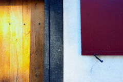 Red shutters and yellow wooden door of an old house Royalty Free Stock Photography