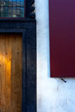 Red shutters and yellow wooden door of an old house Stock Images