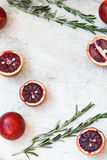 Red Sicilian orange whole and cut on a light background with branches of rosemary. Daylight, open space for your text. Royalty Free Stock Photos