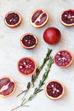 Red Sicilian orange whole and cut on a light background with branches of rosemary. Daylight, open space for your text. Stock Photo