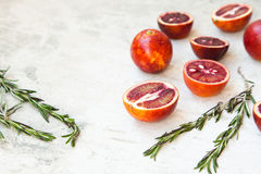 Red Sicilian orange whole and cut on a light background with branches of rosemary. Daylight, open space for your text. Stock Images