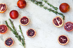 Red Sicilian orange whole and cut on a light background with branches of rosemary. Daylight, open space for your text. Stock Photography