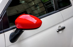 Red side mirror on white car. Stock Photos