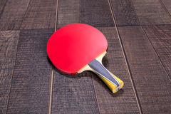 Red side of table tennis bat on wood Stock Photos