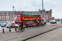 Red sightseeing tour bus and historic houses in Amsterdam, Netherlands Royalty Free Stock Photos