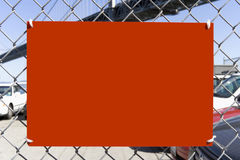 Red Sign Attached to Chain Link Fence Stock Image
