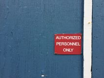 Red sign on blue wooden wall reading authorized personnel only Royalty Free Stock Photography