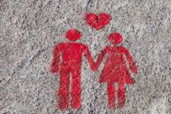 A red sign is drawn on the sidewalk of Porto: the heart, man and woman hold hands. A sign of free space for couples