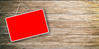 Red sign hanging on wooden background Royalty Free Stock Photos