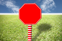 Red sign on the lawn and blue sky. Royalty Free Stock Photo