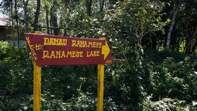Red sign next to green vegetation giving easy direction with yellow letters and arrow towards ranamese lake. Stock Photo