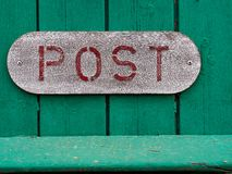 Red Sign Of An Old Vintage Mail Letter Box Post On Green Wood Royalty Free Stock Photography