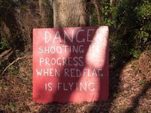 Red sign tree trunk danger shooting is in progress when red flag royalty free stock image