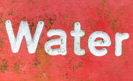 Red signage with the word water painted in white letters. An old metal sign covered in green algae scratches and rust Royalty Free Stock Images