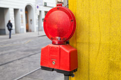 Red signal light on yellow construction area border Stock Photos