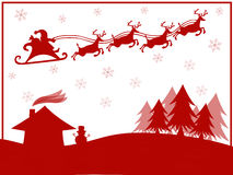 Red silhouette of Santa Claus with reindeer flying over village Stock Photos