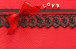 Red silk background with lace and ribbons Stock Image
