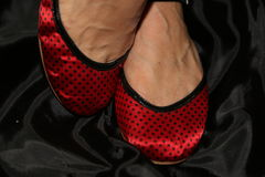 The red silk ballet slippers on a shy ballerina gi Royalty Free Stock Image