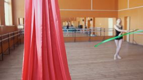 Red silk in front of young woman training a gymnastics exercise with a ribbon. Blurred stock video footage
