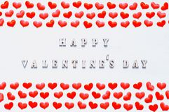 Red silk hearts and inscription Happy Valentines day on the white wooden background. St Valentines day festive background. Red silk hearts and inscription Happy Stock Photo