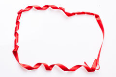 Red silk ribbon, in the form of a frame Royalty Free Stock Photography